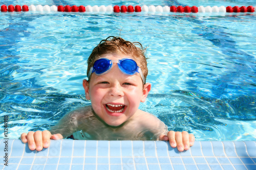 Leinwanddruck Bild Happy child in a swimming pool