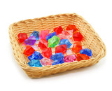 Colored assorted gemstones in wooden basket isolated poster