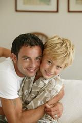 Homme serrant un jeune garçon dans ses bras