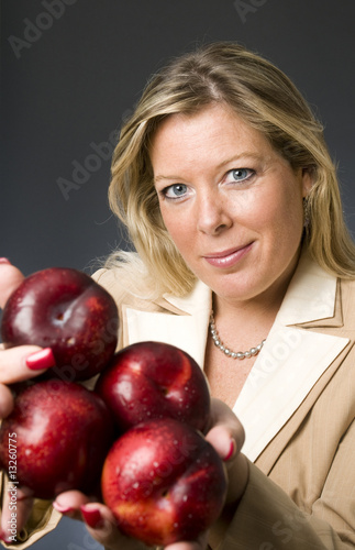 attractive blond woman with plums fruit for healthy life