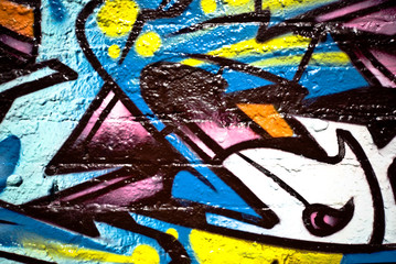 Abstract graffiti detail on the textured brick wall