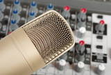 Studio microphone on the audio control console background poster