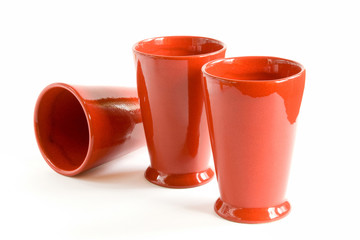 Three red ceramic cups. White background