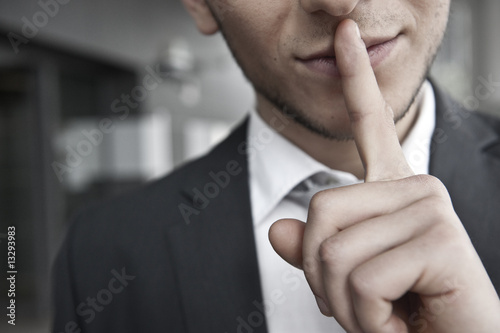 mann mit anzug legt finger auf lippen - 13293983