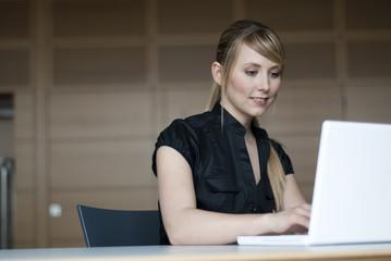 junge frau sitzt vor computer bildschirm