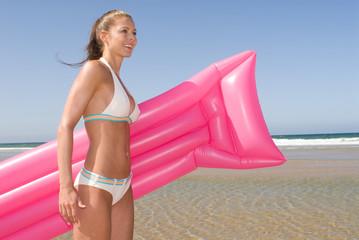 Frau mit Luftmatratze am Meer