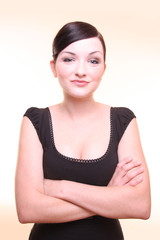 Attractive businesswoman with arms folded, light background