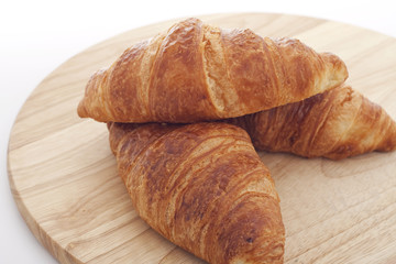 delicious croissants on a wooden cutting board