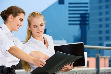 two happy businesswomen with documents