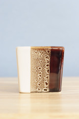 modern coffee mug on wood against blue