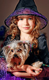 Liitle girl in witch costume with dog