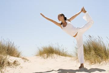 Frau macht Yoga im Sand