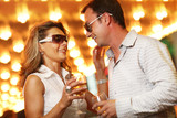 Adult couple enjoying nightlife with glasses of champagne poster