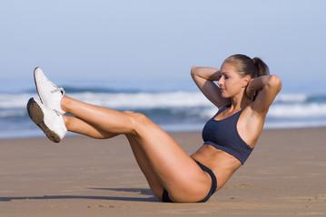 Junge Frau macht Bauchübung am Strand