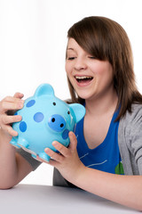 young girl laughing with piggy bank
