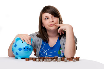 Young girl thinking with money and piggy bank