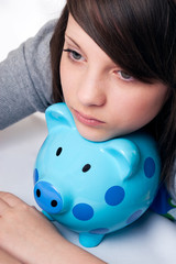 young girl dreaming with piggy bank
