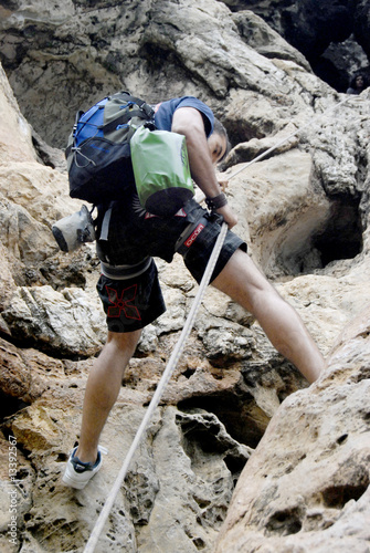 Young man rappeling from a cave in Thailand