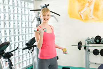 Blonde woman exercising with dumbbell