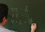 Teacher writing Maxwell's equations on chalkboard