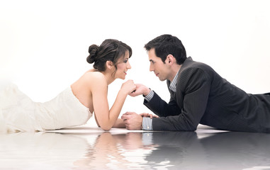 Studio shot of wedding couple, lying on the floor