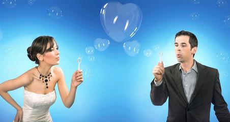 Wedding couple blowing heart shaped romantic soap bubbles