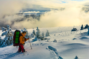Women hiking in winter mountains, surrounded by clouds