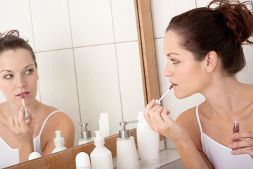 Body care series - Young woman applying lipstick