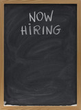 now hiring text on blackboard poster