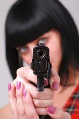 Aiming. Woman with a gun.