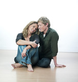 couple souriant assis sur du parquet poster