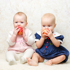 Two infants with apples