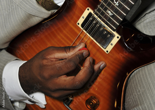 Man Playing Jazz Guitar With Red Pick