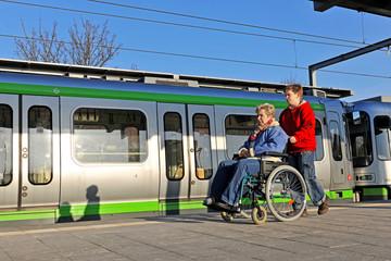 Junge schiebt Frau im Rollstuhl