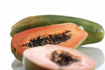 Papaya, ganze Frucht und halbierte Frucht auf weissem Hintergrun