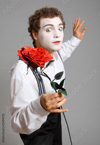 Man holding a rose. mime on grey background