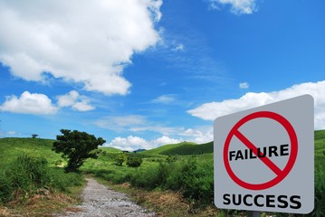 Success signage beside road trail