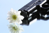 Automatic pistol with white flower on sky background poster