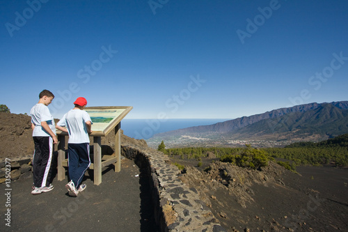 Boys looking at map in volcanic landscape