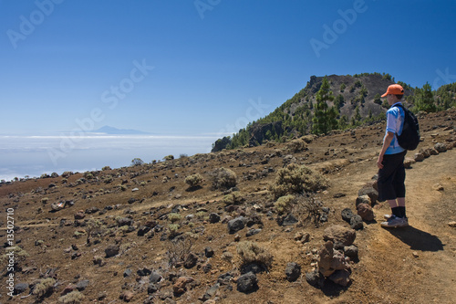 Boy looking at Tenerife from volcanic landscape La Palma