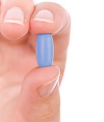 Hand holding a blue pill close up.
