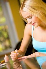 Portrait of young beautiful woman making manicure