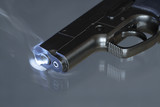 Automatic pistol after shooting on dark background poster