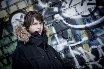 The young guy in a jacket with a hood costs near a wall