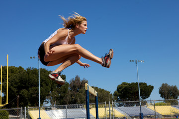 Athletic girl hurdling at the track