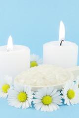 daisies, candles and bath salt over blue