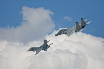 An F-15 Strike Eagle and an F-16 Fighting Falcon do a flyby
