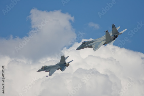 Fotobehang Luchtsport An F-15 Strike Eagle and an F-16 Fighting Falcon do a flyby