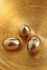 drei goldene Eier auf goldener Schale
