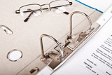 glasses and open binder with invoice poster